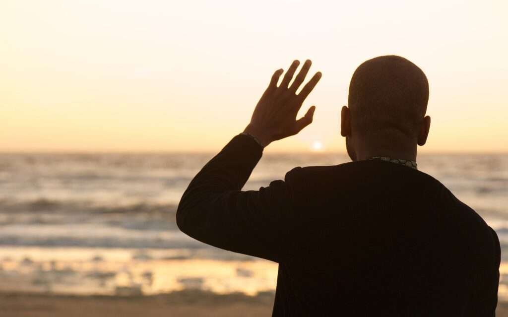 Man waving at the sunset